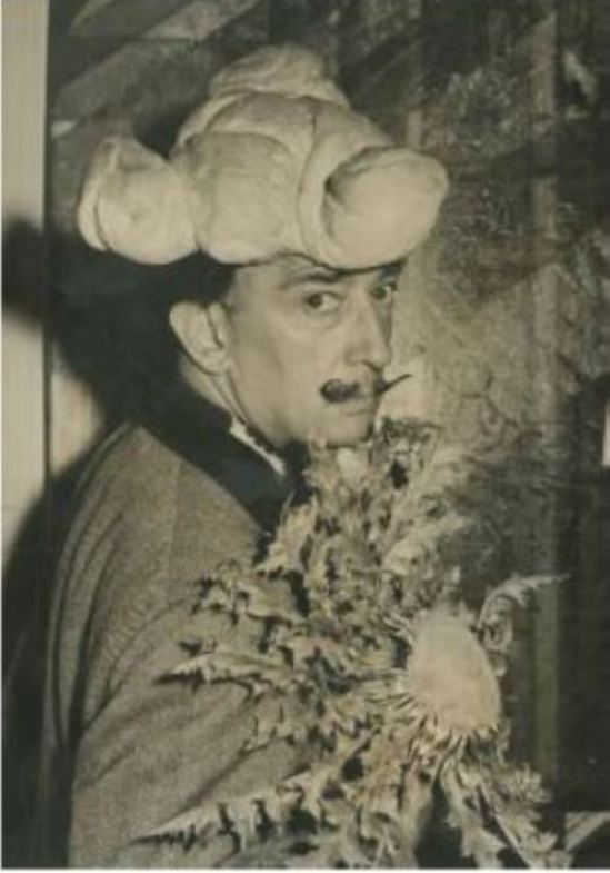 Salavador Dali coiffé d'un chapeau de pain et tenant un tournesol 1958