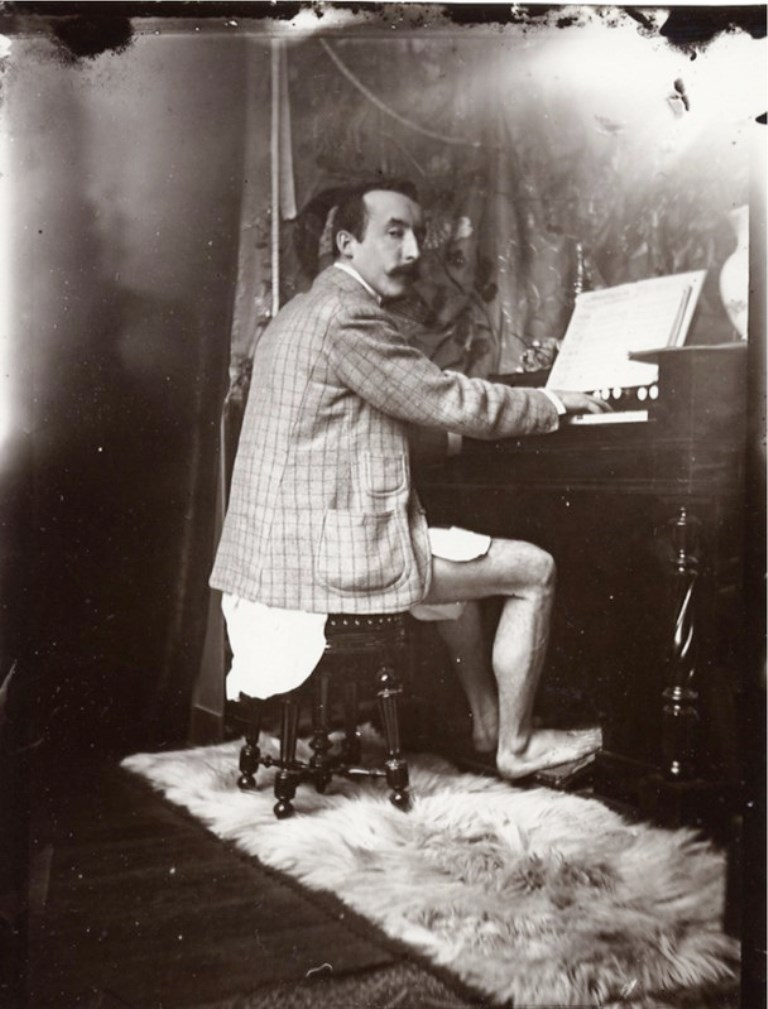 Alphonse Marie Mucha. Paul Gauguin playing Mucha's harmonium in his studio, Rue de la Grande Chaumière, Paris 1893-1894 Via muchafoundation
