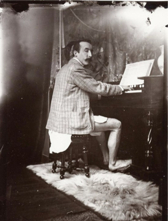 Alphonse Marie Mucha. Paul Gauguin playing Mucha's harmonium in his studio, Rue de la Grande Chaumière, Paris 1893-1894 Via muchafoundation