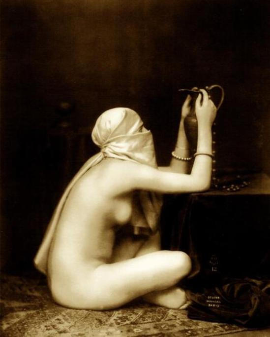 Julian Mandel. A veiled harem woman sitting cross legged and holding a jug 1920 Via odalisques