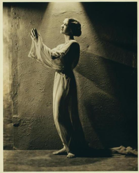 Nickolas Muray. Isadora Duncan in costume, standing in a halo of light, hands lifted as if in prayer Via nypl