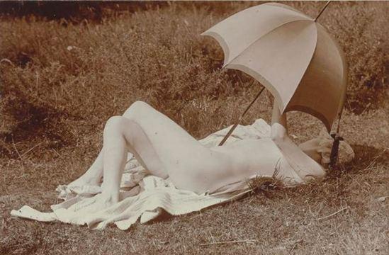 Charles Augustin Lhermitte. Jeune femme nue dans un pré se reposant à l'ombre d'une ombrelle vers 1912. Via RMN