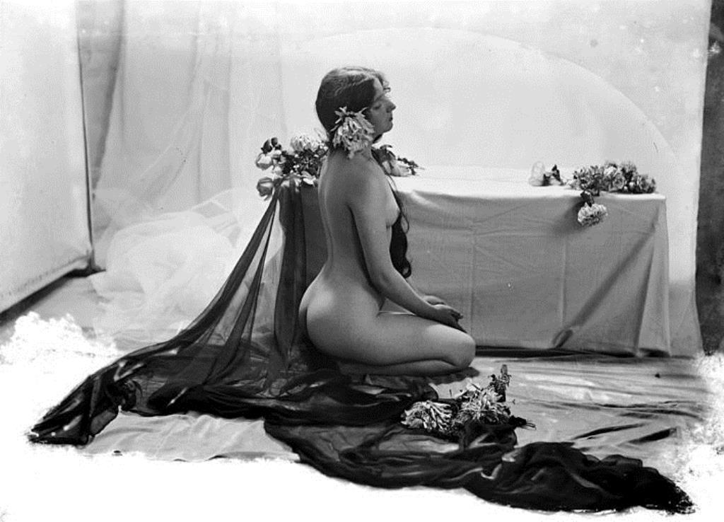 Émile Joachim Constant Puyo. Mise en scène d'un modèle féminin, jeune femme nue, vue de trois-quart dos, assise au sol, à côté d'un coffre, le voile noir installé dans le décor. Via rmn