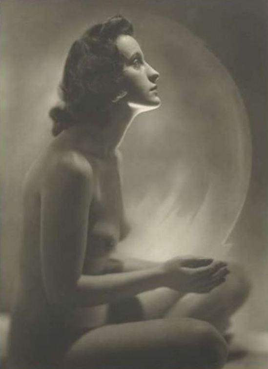Jacob Merkelbach. Naakte zittende wrouw met de handen opgehouden naar een wit ingeschilderde cirkel licht 1925-1945