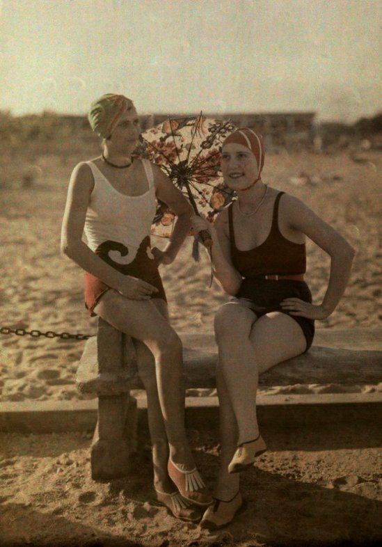 Two women in bathing suits sit on a bench.